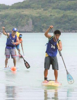 終盤で加藤勇人(左奥)を追い抜いてゴールへ向かう前瀬有佑(手前右)=22日午前、底地ビーチ