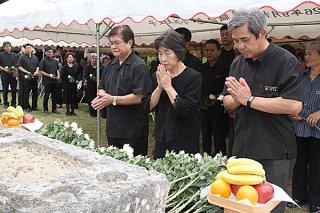 明和大津波で亡くなった人々の冥福を祈り、花をささげる参列者=24日午後、明和大津波慰霊塔