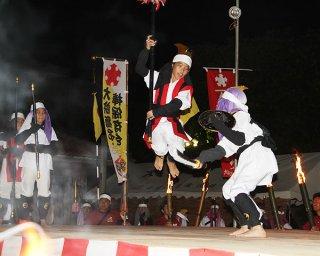 たいまつが照らす特設ステージで、堂々と棒術を披露する子どもたち=28日夕、崎原公園