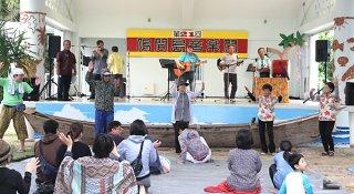 悪天候の中、第21回鳩間島音楽祭に集まった人たち。ゆったりと舞台の音楽を楽しんだ=3日午後、鳩間島公民館前野外ステージ