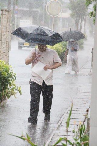 雨の中、傘をさして足早に移動する人々=8日、石垣市登野城