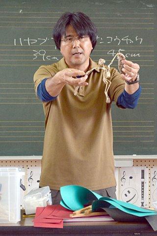 リュウキュウコノハズクの骨格標本を見せながら、鳥の体の構造などを説明する佐野清貴さん=9日午前、大本小