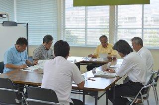 市不登校対策等支援員配置モデル事業の配置校検討委員会で話し合う委員たち=7日午後、市教委