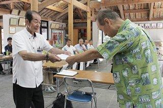 計画案が池田孝之委員長(右)から西大舛髙旬町長に答申された=18日午後、竹富島まちなみ館