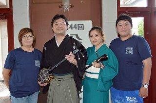 横目貞子さん(左)から指導を受け、新人賞の部に初挑戦した張裕祥さん(同2人目)と陳咏織さん(同3人目)。右端は審査を見学した官岩碩さん=9日午後、市民会館中ホール
