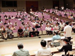 住民意見交換会に参加する市民。冒頭、中山義隆市長のあいさつを聞く=11日夜、石垣市民会館大ホール