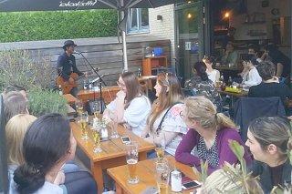 ハンブルク市内のオープンカフェで演奏する前花雄介=5月23日午後、「Fele」(前花雄介提供)