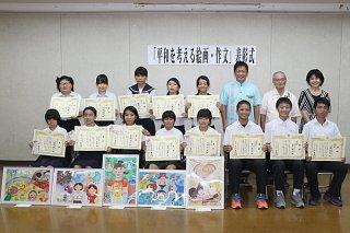 「平和を考える」絵画・作文コンテストで入賞した児童生徒ら =15日午後、市役所