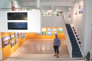 20日にオープンする石垣初の写真美術館「MIRA」と代表の井戸巌也さん=16日午前、同館