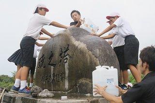 「慰霊の日」を前に水を掛けて暁之塔を磨く川原小学校の児童ら=22日午前、暁之塔