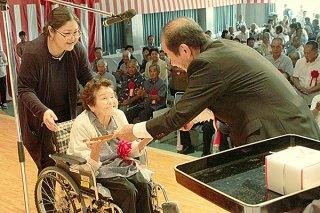 竹富町制施行70周年記念式典で、町発展に尽力したとして表彰を受ける功労者ら=2日午前、中野わいわいホール