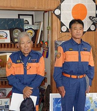 石垣市消防団長の退任辞令を受け、あいさつする新垣能一氏(左)。右は新団長の狩俣武市氏=3日午前、市長室