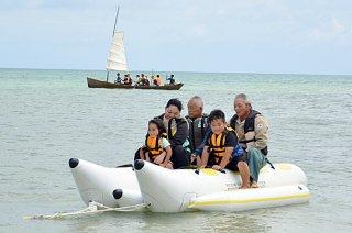 チャリティー祭りで、バナナボートやサバニ(後方)を楽しむ参加者=7日午前、平久保