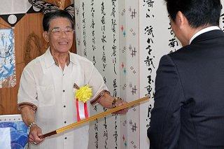 中山義隆市長から地方自治部門の市政功労賞を受ける東民雄氏(左)=10日午前、市長室