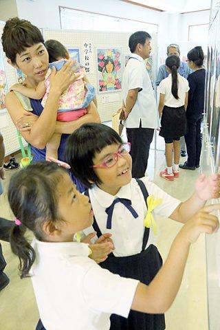 開会セレモニー終了後、展示会場で入選作品を鑑賞する児童や保護者ら=13日午前、八重山平和祈念館