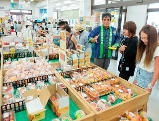 買い物客にマンゴーをPRするマンゴー生産部会の友利和博部会長(右から3人目)=14日午前、ファーマーズマーケットゆらてぃく市場
