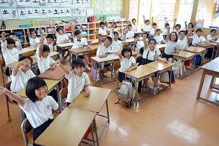 「夏休みも勉強や運動を頑張るぞ!!」と気合を入れる登野城小学校3年3組の児童たち=20日午前、同校