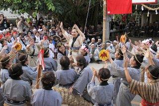 棒貫人(ブルピトゥ)の仲大範子さんが雌雄の綱に棒を差し込んだあと、ガーリィで祝福する婦人ら=7月31日夕、真乙姥御嶽前
