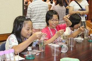 ㈱ユーグレナのブースで、微細藻類を用いた実験を体験する児童ら=5日午後、石垣市健康福祉センター検診ホール