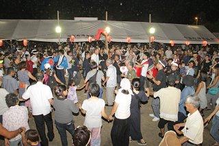 手をつないで輪を作り巻踊りを踊る住民や観光客ら=11日夜、大原公民館前広場