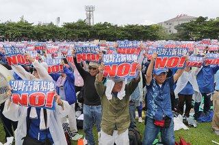 辺野古新基地反対を訴えるメッセージボードを掲げる参加者ら=11日午前、那覇市の奥武山陸上競技場