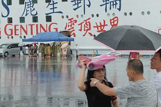 下船後、テントで待機する乗客(奥)と、傘を差すなどしてレンタカーを予約しようと右往左往する乗客(手前)=16日午前、南ぬ浜町のクルーズ船専用岸壁