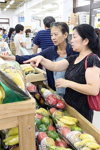 旧盆準備で供え物などを買い求める人たち=22日午後、JAファーマーズマーケットゆらてぃく市場