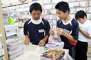 漫画本にシュリンクがけをする大城碧君(手前左)と船道海静君(同右)=5日午前、Booksきょうはんやいま店