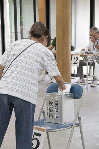 竹富町議会議員選挙で1票を投じる有権者。全体で投票率は86・64%と過去最低を記録した=9日午後、竹富まちなみ館