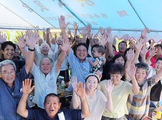 初孫の律斗ちゃん(10カ月)を抱っこして万歳三唱で喜びを分かち合う大久研一氏(中右)=10日夕、自宅庭の祝賀会場