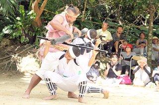 「三人棒」奉納で大男の棒を受け止める中学生=17日午後、川平の群星御嶽