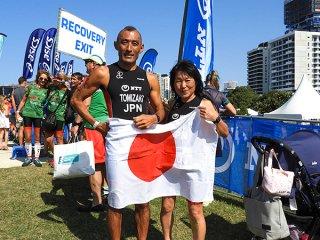 ITU世界トライアスロン大会への出場を果たし笑顔を見せる富崎義明(左)と川原千賀子=16日、ゴールドコースト(チーム冠鷲提供)