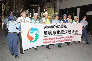 パレードで環境浄化を呼び掛ける八重山地区安全なまちづくり推進協議会など関係団体ら=26日夜、美崎町