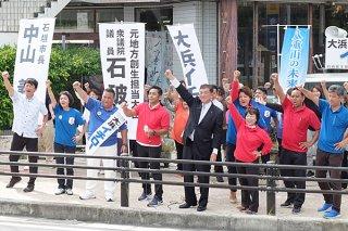 石破茂氏(中央右)とともに「頑張ろう」をする佐喜真・大浜陣営の支持者ら=27日午前、730交差点