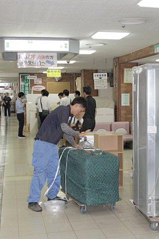 30日の入院患者移送を前に、引っ越し作業を進める運送業者=29日午後、八重山病院内