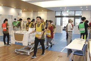 新八重山病院に続々と移送される入院患者。移送チームがそれぞれの病棟に移動させた=9月30日午後、同院
