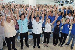 当選を確実にし、万歳を三唱する大浜一郎氏(中央)と支持者ら=9月30日午後9時すぎ、真栄里の選対事務所