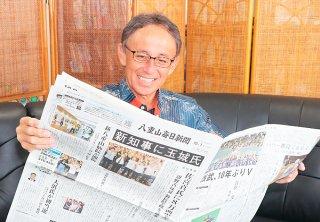 新知事誕生を伝える新聞に笑顔で目を通す玉城デニー氏=1日午後、那覇市内