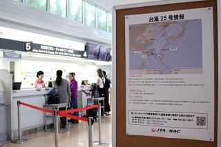 台風25号の接近に伴い台風情報が掲示される南ぬ島石垣空港。カウンターでは予約変更や振り替えなどの手続きをする人たちの姿が見られたれた=4日午前