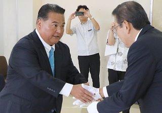 当選証書を受け、握手をする大浜一郎氏=4日午前、県庁