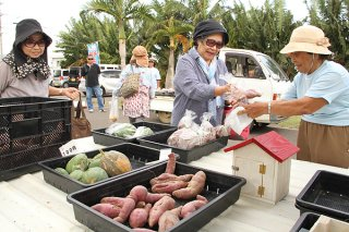 名蔵軽トラ市で農産物を購入する客ら。約1時間半で完売した=6日午前、名蔵公民館広場