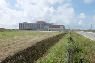 新県立八重山病院(奥)と市道を挟んで隣接する石垣市役所新庁舎の建設地。着工のメドは立っていない=7日午前