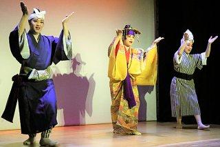 ゆいロードシアターで始まった定期公演の初舞台で「安里屋ユンタ」を披露する八重山芸能団「世乞い」の出演者ら=9日午後、同シアター