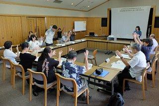 委員長あいさつの後、手話で拍手を送る委員ら=23日午後、石垣市立図書館2階視聴覚室