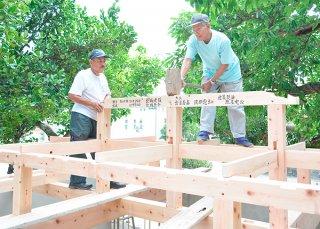 真乙姥嶽拝殿の上棟式で、棟木を取り付ける大工の宮良善嘉さん(中央)と漢那憲吉さん=29日午後、同嶽