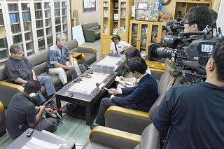 県内外メディアから今後の対応について取材を受ける外間守吉町長(左から2人目)=30日午後、町長室