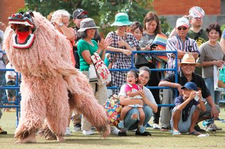 オープニングセレモニーの幕開けを飾る白保子ども獅子会の獅子舞。来場者も大喜びだった=3日午前、新栄公園