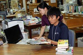 石垣市立図書館で就業体験をする八重山高校1年の金嶺隼君(手前)=6日午前、石垣市立図書館