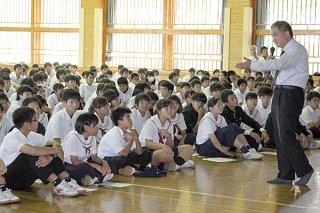 高宮城修氏(右)から、スマホやゲームが脳に与える影響などについて説明を受ける大浜中の生徒たち=15日午後、同校体育館