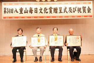 八重山毎日文化賞の正賞を受賞した八重洋一郎さん(左から2人目)、當山善堂さん(同3人目)、特別賞を受賞した玉城功一さん(右端)、奨励賞を受賞した宮良断さん=18日午前、アートホテル石垣島